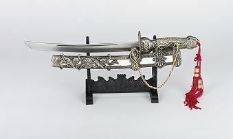 Dekorations-Samuraischwert  Der Griff und die Scheide sind aus Metall, die Scheide hat eine Holzeinlage. Gesamtlänge 37 cm  mit rostfreien Klingen.  Die Griffe und die Scheiden sind reich verziert. mit Kunststoffständer geliefert. Preiswerte kleine Dekorations-Samuraischwerter